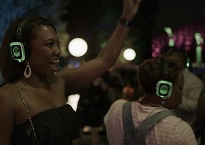 woman dancing while wearing silent disco headphones